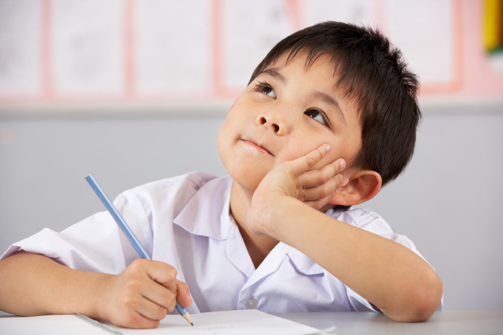 Boy sitting at a desk, thinking